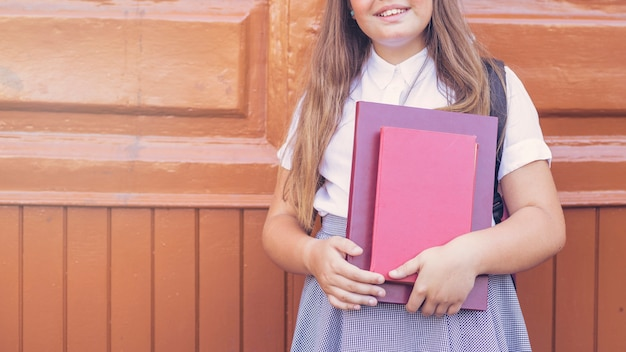 Écolière en uniforme tenant des livres et souriant Photo gratuit