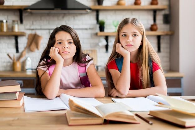 Écolières multiethniques ennuyés à faire leurs devoirs Photo gratuit