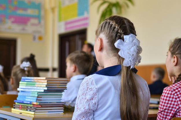 Les écoliers des enfants sont assis à leur bureau dans la classe de l'école Photo Premium