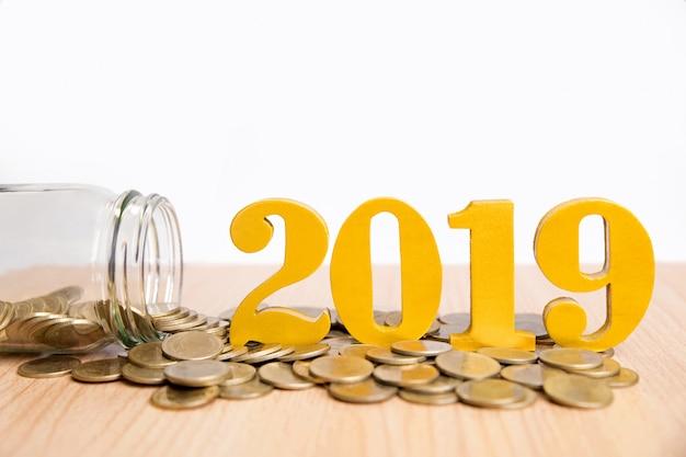 Économies nouvel an concept.word 2019 mettre des pièces et des bouteilles en verre avec des pièces à l'intérieur Photo Premium