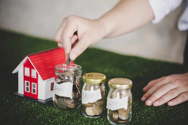 Économiser de l'argent pour la maison dans la bouteille en verre Photo Premium