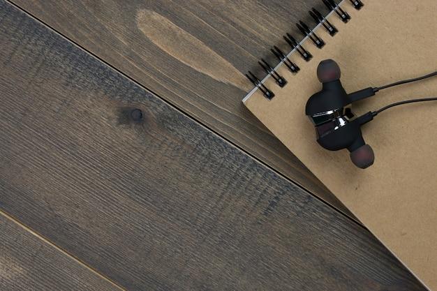 Écouteurs et cahier sur le bureau en bois avec espace de copie. Photo Premium
