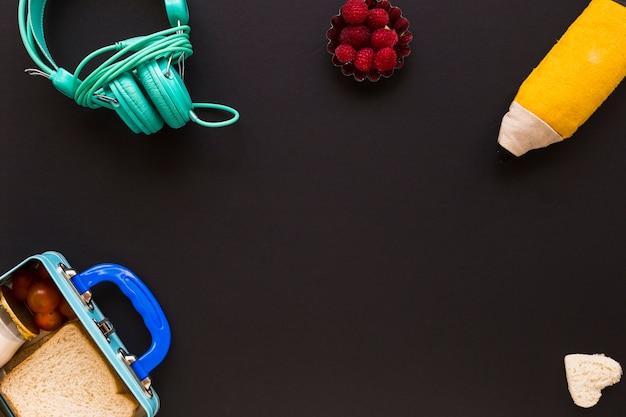 Écouteurs et étui à crayons près de la boîte à lunch Photo gratuit