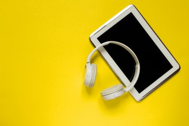 Des écouteurs modernes et une tablette blancs sur fond jaune et plat, vue de dessus, à l'arrière-plan jaune tendance pour texte Photo Premium