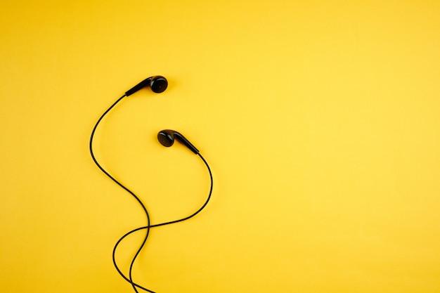 Écouteurs Noirs Sur Jaune Chaud à La Mode. Concept De Style De Vie De Musique. Copie Espace. Pose à Plat Photo Premium