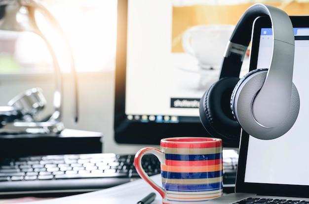 Les écouteurs sont suspendus sur un écran d'ordinateur portable avec un écran vide Photo Premium