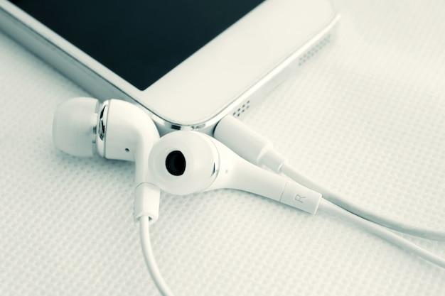 Écouteurs et téléphone portable sur fond de table blanche Photo Premium