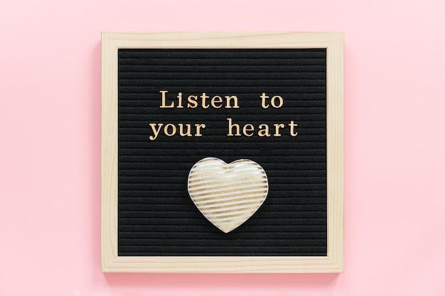 Écoutez Votre Cœur. Citation De Motivation En Lettres D'or Et Coeur Textile Décoratif Sur Tableau Noir Sur Fond Rose. Photo Premium