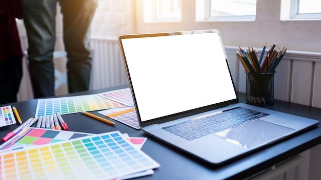 Écran d'ordinateur portable blanc vierge de graphistes mis sur la table de bureau en co-working Photo Premium