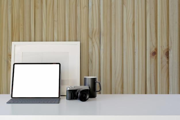 Écran d'ordinateur tablette vierge sur le lieu de travail devant un mur en bois avec espace de copie Photo Premium