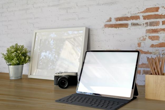 Écran d'ordinateur tablette vierge sur le lieu de travail en face sur le vieux mur de briques blanches avec espace de copie Photo Premium