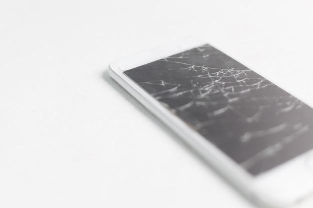 Écran de téléphone portable cassé, éclats dispersés. Photo Premium