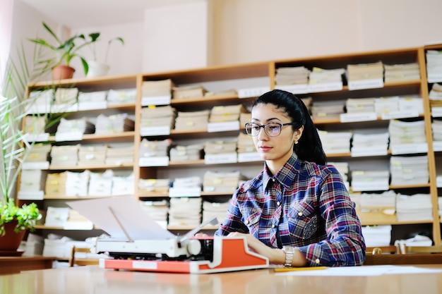 Écrivain mignon jeune femme à lunettes est en train de taper sur une machine à écrire dans la bibliothèque de fond Photo Premium