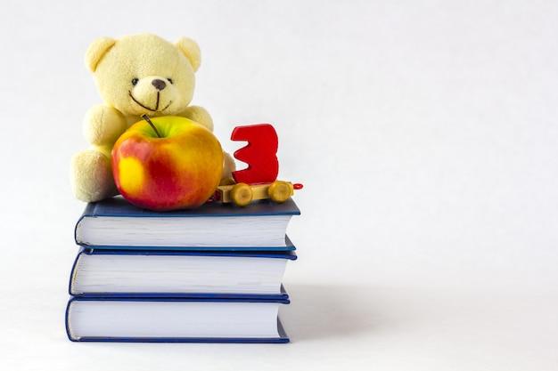 L'éducation Ou La Rentrée Scolaire. Une Pomme Et Un Ourson Et Un Jouet En Bois En Forme De Nombre Sur Une Pile De Livres Sur Un Fond Blanc Photo Premium