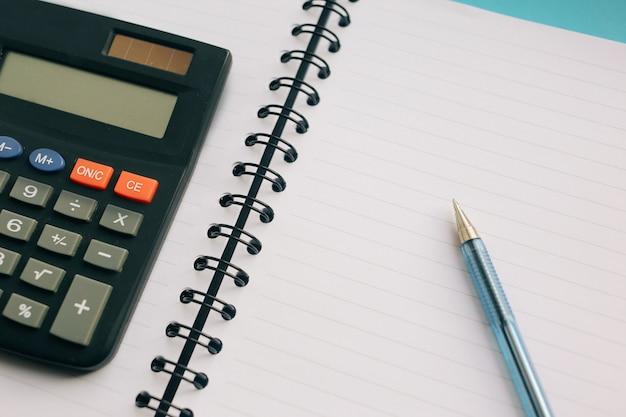 Effacer Le Cahier, Stylo Et Une Calculatrice Sur Un Fond Bleu Photo Premium