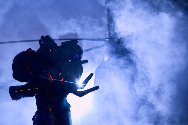 Effrayant gros robot devant un hélicoptère militaire dans un nuage de fumée. Photo Premium