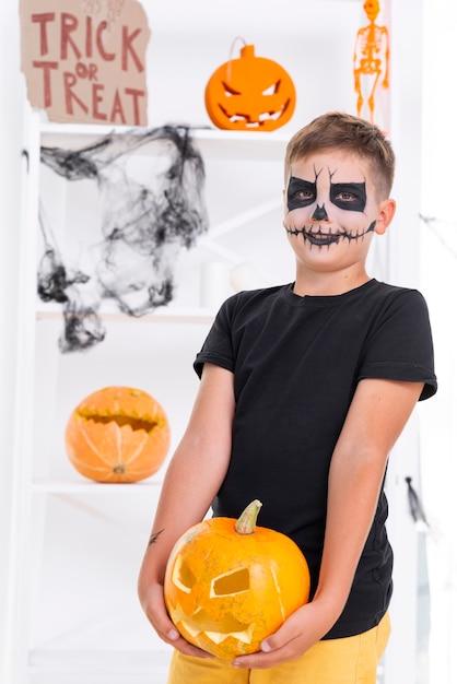 Effrayant jeune garçon tenant la citrouille d'halloween Photo gratuit