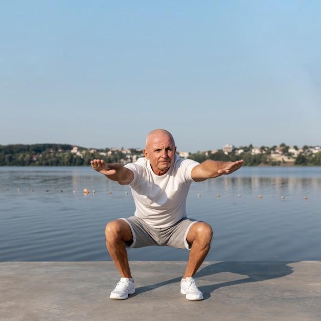 Elder Stretching Outors Regardant La Caméra Photo gratuit