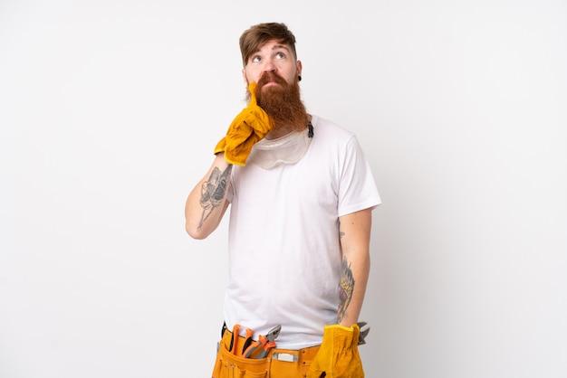 Électricien Rousse Avec Longue Barbe Sur Mur Blanc Isolé En Pensant à Une Idée Photo Premium