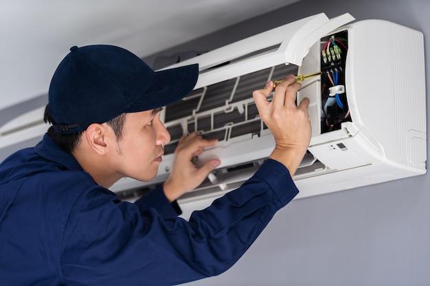 Électricien avec tournevis réparant le climatiseur à l'intérieur Photo Premium