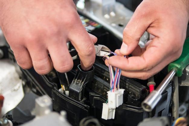 Électricien de voiture répare la voiture, le testeur et les fusibles et les pinces Photo Premium