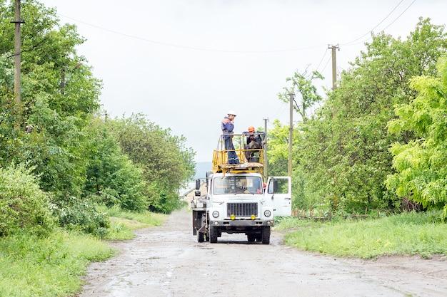 Électriciens travaillant sur des poteaux, un groupe de travailleurs dans des véhicules spéciaux Photo Premium