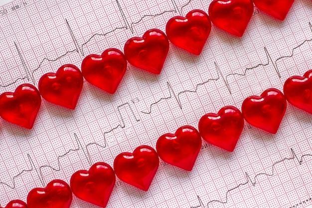 Électrocardiogramme et coeurs rouges. Photo Premium