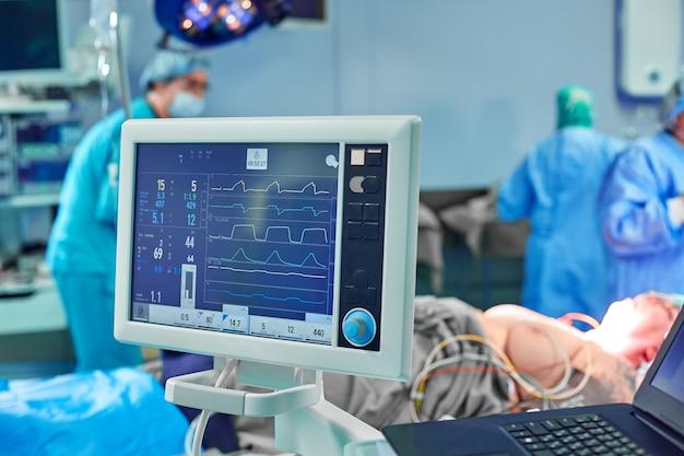 Électrocardiogramme en salle d'opération de chirurgie à l'hôpital montrant la fréquence cardiaque du patient avec une équipe floue de chirurgiens Photo Premium