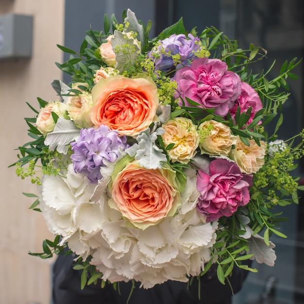 Un élégant bouquet de fleurs blanches, orange, jaunes et violettes avec des feuilles vertes décoratives Photo gratuit