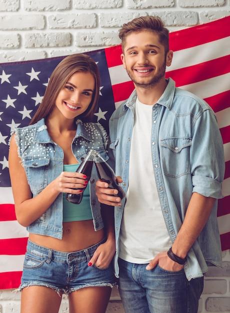 Élégant couple d'adolescents tenant une bouteille d'eau gazeuse Photo Premium