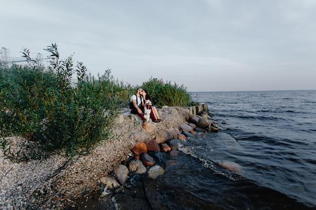 Élégant Couple D'amoureux Assis Au Bord De La Mer Avec Deux Chiens Blancs Photo Premium