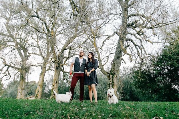 Élégant couple amoureux dans le parc avec leurs deux chiens blancs Photo Premium
