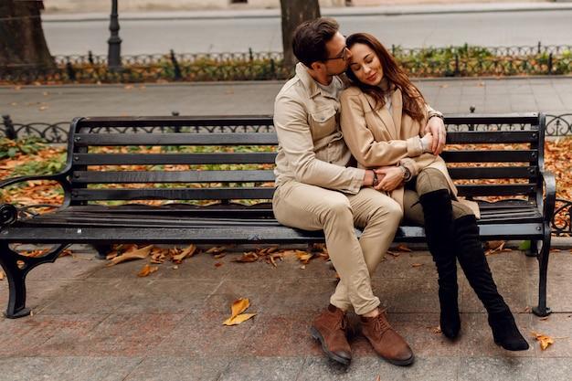 Élégant Couple Amoureux Posant En Plein Air. Tendances De La Mode D'automne. Modèle Brune Avec Un Mec élégant En Manteau Beige Assis Sur Un Banc. Photo gratuit