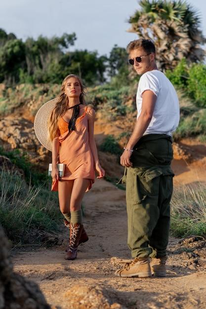 Élégant couple hipstersa, jeune homme vêtu d'un t-shirt blanc, de lunettes et d'un pantalon large, d'une jeune fille vêtue d'une large robe, de bottes décontractées et d'un chapeau dans le dos. boho style outdoor Photo Premium