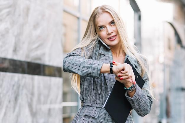 Élégant, femme affaires, regarder montre Photo gratuit