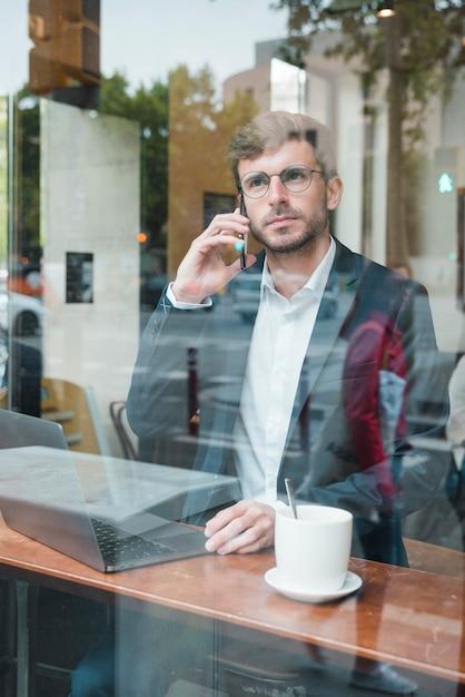 Élégant jeune homme d'affaires, parler au téléphone portable au café Photo gratuit