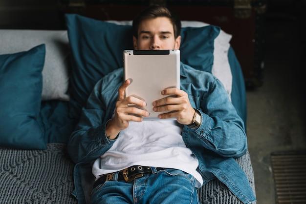 Élégant Jeune Homme Allongé Sur Le Lit En Regardant Une Tablette Numérique Photo gratuit