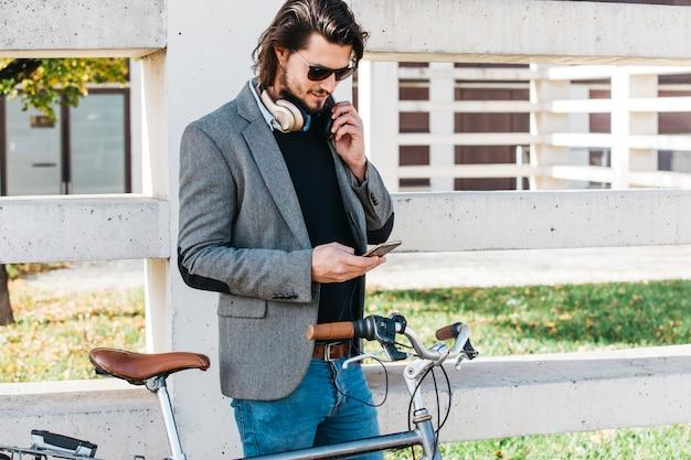 Élégant jeune homme debout près du vélo à l'aide de téléphone portable Photo gratuit