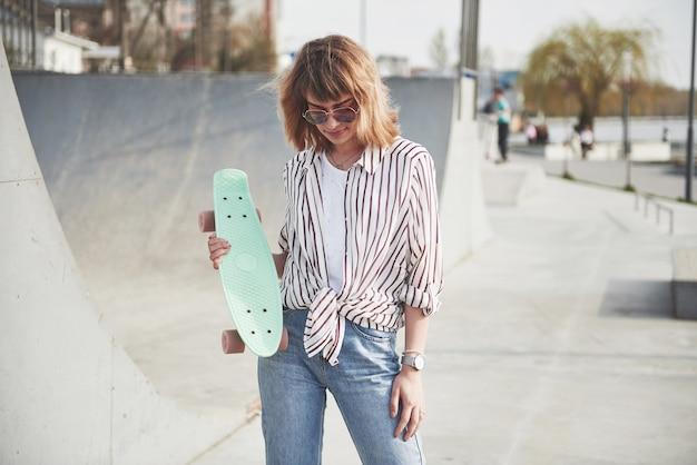 Élégante Belle Jeune Femme Avec Une Planche à Roulettes, Sur Une Belle Journée Ensoleillée D'été. Photo gratuit