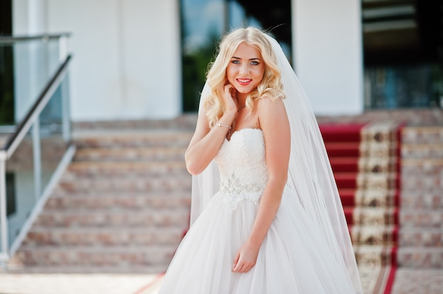 Elégante Blonde Aux Yeux Bleus Fashion Mariée Au Grand Hall De Mariage Sur Le Tapis Rouge Photo Premium