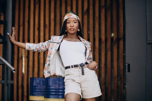 Élégante femme afro-américaine dans le parc sur le fond en bois Photo gratuit