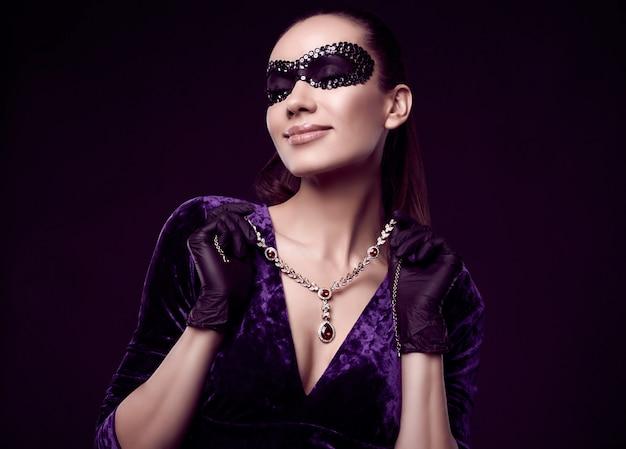 Élégante Femme Brune En Belle Robe Violette, Masque De Paillettes Et Gants Noirs Photo gratuit