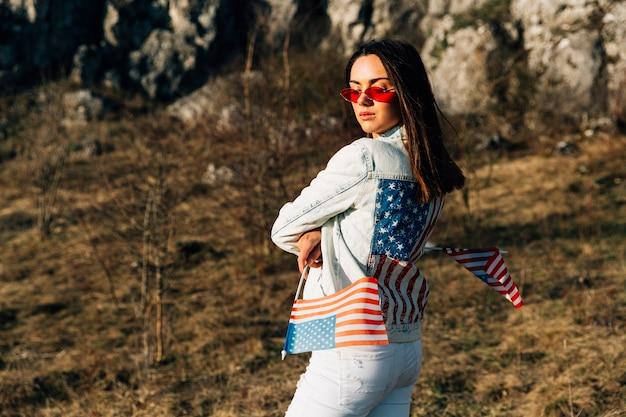 Élégante femme debout sur la nature avec des drapeaux des états-unis Photo gratuit