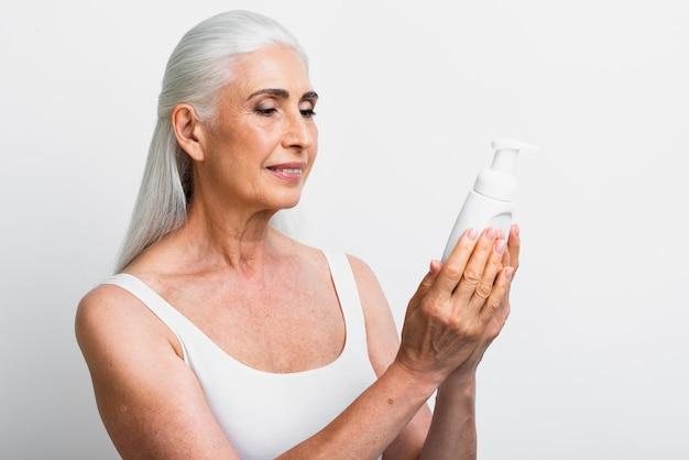 Élégante femme mûre tenant un produit de soin de la peau Photo gratuit