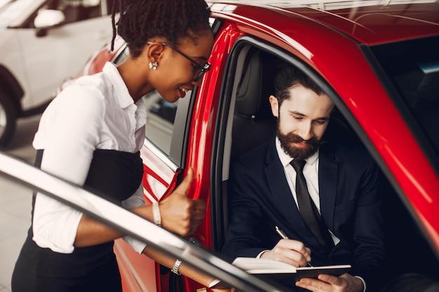 Élégante femme noire dans un salon de l'automobile Photo gratuit