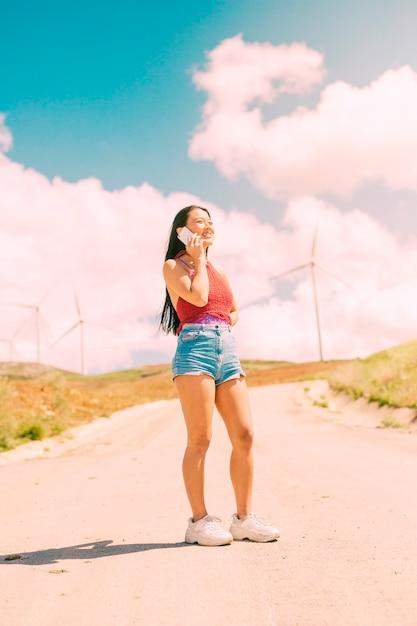 Élégante femme téléphonant sur une route rurale Photo gratuit