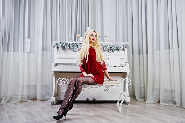 Elegante Fille Blonde Porter Sur La Robe Rouge Posée Contre Le Piano En Studio. Photo Premium