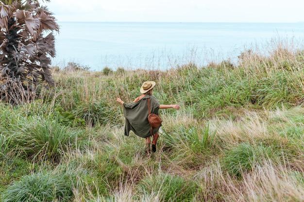 Élégante jeune femme en chemise kaki marchant dans les steppes, voyageant en afrique en safari, portant chapeau et sac à dos marron, explorant la nature, temps ensoleillé. style boho. vue arrière Photo Premium