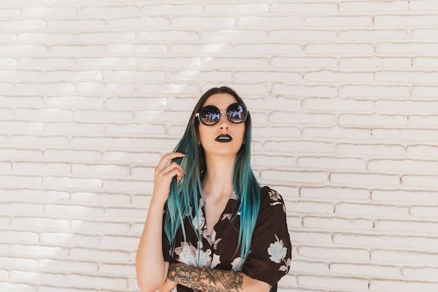 Élégante jeune femme avec les cheveux teints, debout devant le mur beige Photo gratuit