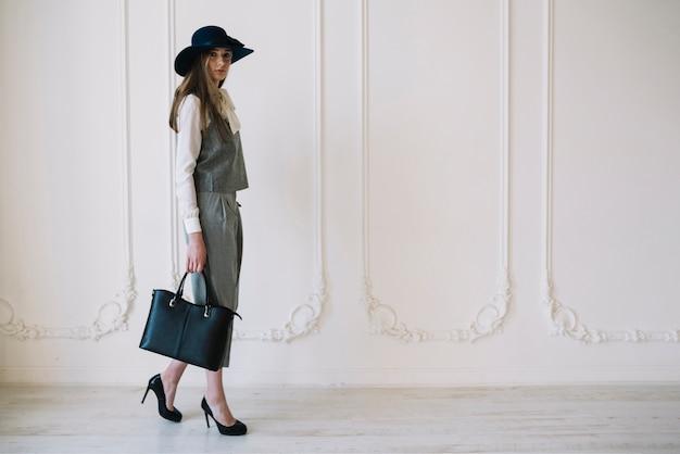 Élégante jeune femme en costume et chapeau avec sac à main dans la chambre Photo gratuit